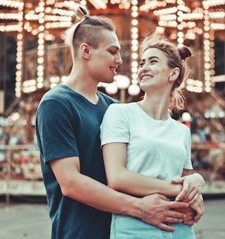 Giovani coppie nell'amore divertendosi insieme al parco di divertimenti