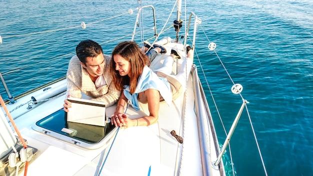 Giovane coppia innamorata che si diverte con il tablet pc sulla barca a vela - stile di vita di viaggio di lusso e concetto di nomade digitale su un esclusivo tour in yacht - filtro vivido luminoso con distorsione morbida dell'obiettivo fisheye