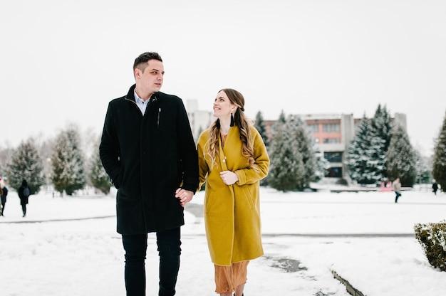 Giovani coppie nell'amore che tengono le mani all'aperto. l'uomo e la donna camminano su un parco invernale innevato nel concetto di amore e tempo libero.