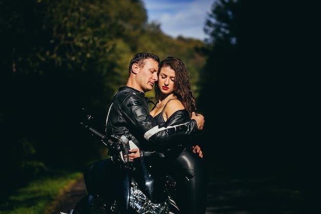 Giovane coppia innamorata abbracciare e baciare vicino a una moto sportiva nera sullo sfondo di una strada forestale