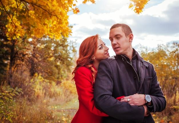 Giovane coppia innamorata abbracci nella foresta autunnale tra alberi colorati. appuntamento romantico