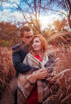 Giovane coppia innamorata abbracci nella foresta autunnale tra erba alta. gente felice che sorride