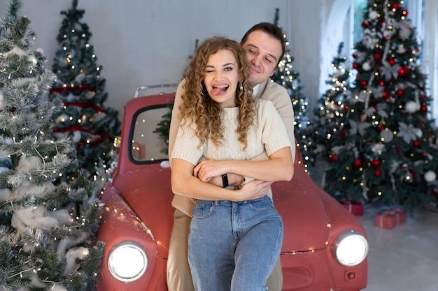 Giovane coppia innamorata ridendo e celebrando il natale vicino all'auto rossa
