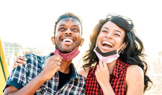Giovani coppie nell'amore che ride sopra la maschera facciale aperta
