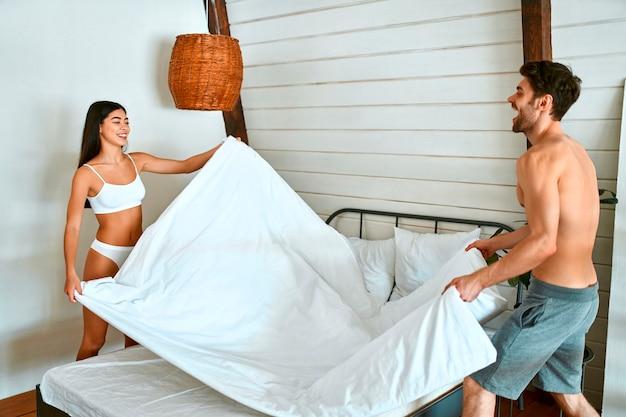 Una giovane coppia innamorata fa un letto in una camera da letto moderna e luminosa. la routine mattutina della coppia.