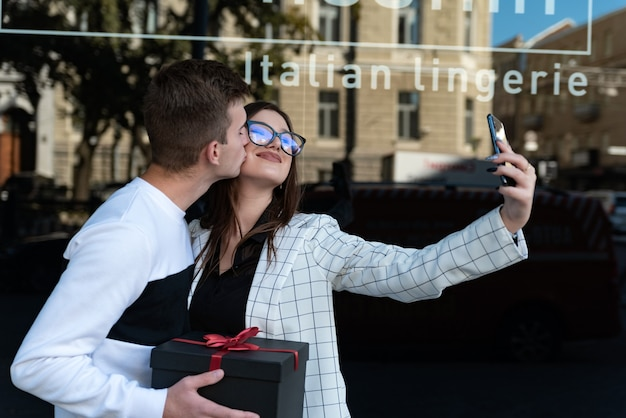 La giovane coppia innamorata fa selfie con un regalo nelle loro mani. guy fa un regalo alla sua ragazza e la bacia. sorridente coppia innamorata.