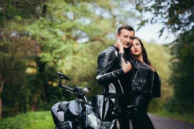 Giovane coppia innamorata su una moto sulla strada nel bosco
