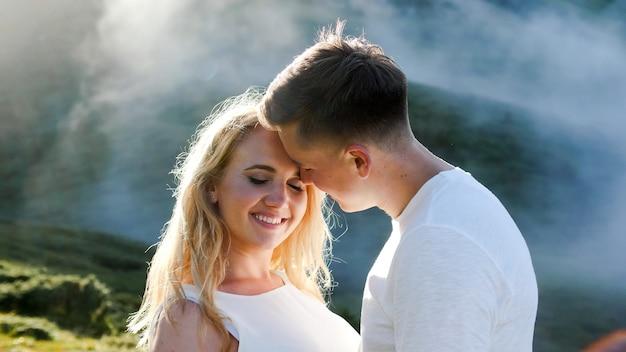 Giovane coppia innamorata su un prato di montagna sullo sfondo di nebbia e sole.