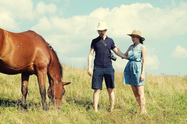 Giovani coppie nell'amore all'aperto. ritratto all'aperto sensuale sbalorditivo di giovani coppie che posano nel tramonto di estate vicino al cavallo.