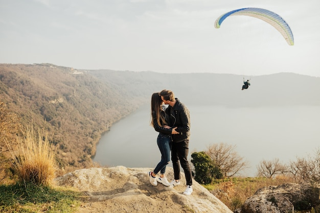 Giovani coppie nell'amore all'aperto che abbracciano e che ridono insieme al lago e alla montagna