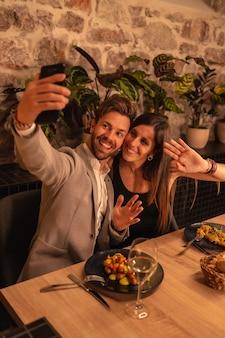 Una giovane coppia innamorata in un ristorante, divertirsi cenando insieme, festeggiare san valentino, scattare un selfie ricordo