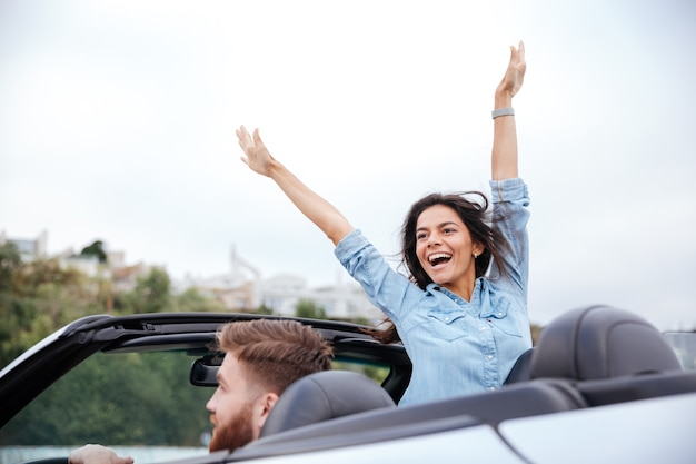 Giovane coppia innamorata in viaggio su strada guidando in auto convertibile