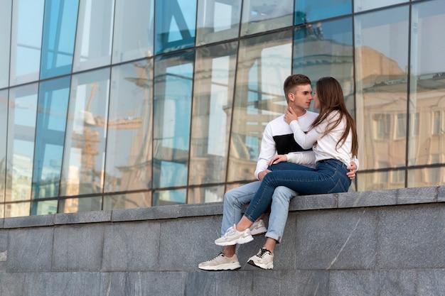 La giovane coppia innamorata si siede fuori dall'edificio e sussurra. la ragazza è seduta sulle ginocchia del ragazzo e lo abbraccia. amore studentesco.