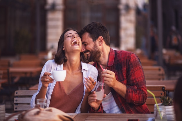 Giovane coppia innamorata seduta in un bar e divertirsi