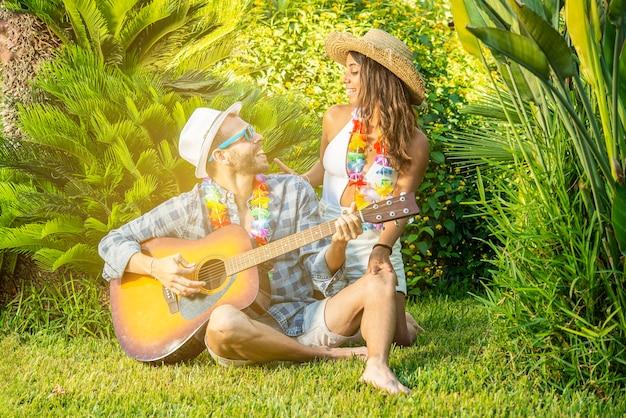 Giovane coppia innamorata seduta sull'erba a suonare la chitarra. concetto di amore e felicità