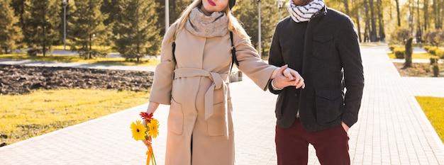 Giovane coppia innamorata che cammina nel parco autunnale tenendosi per mano.