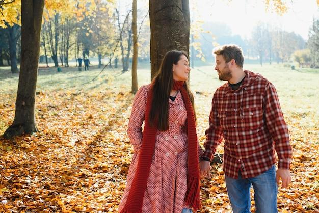 Giovane coppia innamorata che cammina nel parco autunnale tenendosi per mano