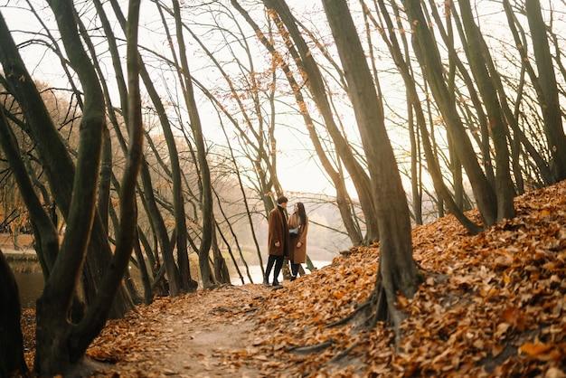 Giovane coppia innamorata che cammina nel parco in una giornata autunnale