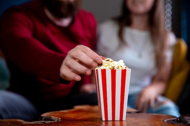 Una giovane coppia innamorata guardando la televisione di notte appuntamento romantico notte sdraiata sul divano a mangiare popcorn