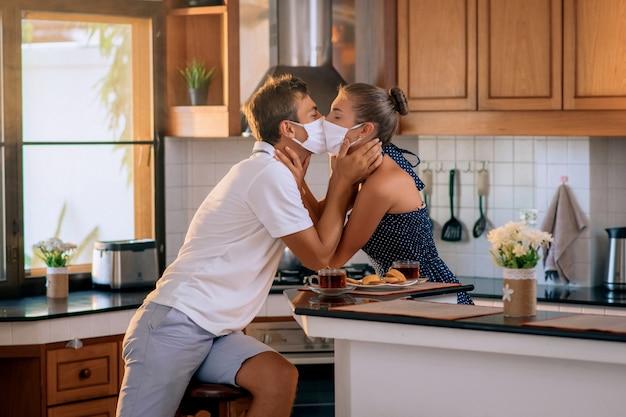 Giovane coppia innamorata indossa maschere protettive e si baciano in cucina, pandemie e sentimenti.