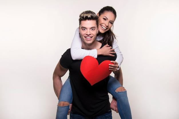 Giovane coppia innamorata di un grande cuore rosso isolato su sfondo bianco