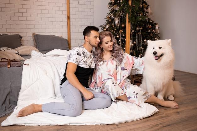 Giovane coppia innamorata di un cane samoiedo seduto sul pavimento vicino al letto di casa sull'albero di natale sullo sfondo