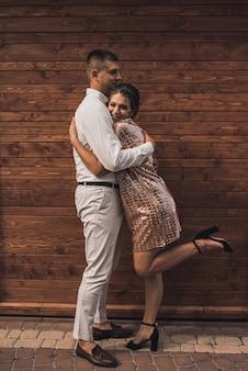 La giovane coppia di amanti uomo e donna in abiti alla moda festivi sta abbracciando. acconciatura casual leggera per donne con permanente. sfondo di legno marrone della plancia