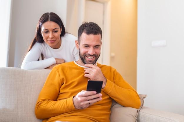 Coppia giovane sdraiato a casa. uno di loro usa il telefono e flirta.