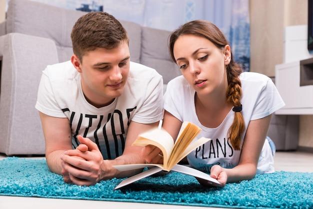 Giovane coppia sdraiata su un tappeto nel loro soggiorno e leggendo un libro in un'atmosfera rilassata