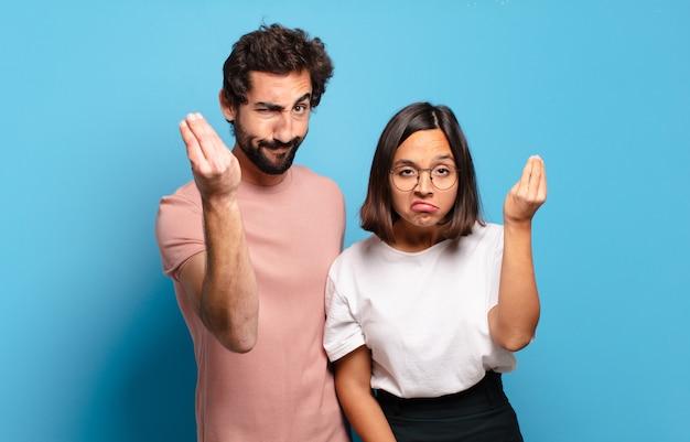 Giovani coppie che fanno capice o gesto dei soldi, dicendoti di pagare i tuoi debiti!