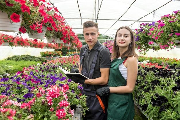 Giovani coppie che prendono appunti negli appunti nella stagione primaverile mentre si lavora con le piante nella loro serra