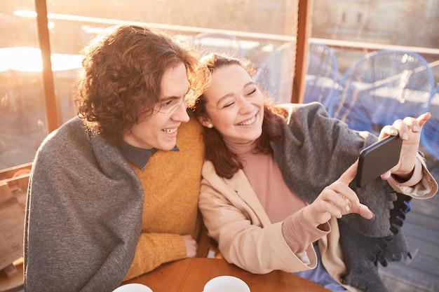 Giovani coppie che fanno selfie ritratto sul telefono cellulare durante la loro data nella caffetteria