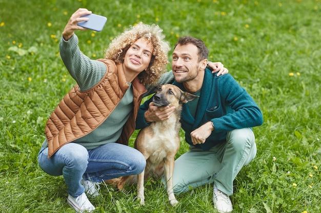Giovani coppie che fanno selfie ritratto sul telefono cellulare con il loro animale domestico all'aperto