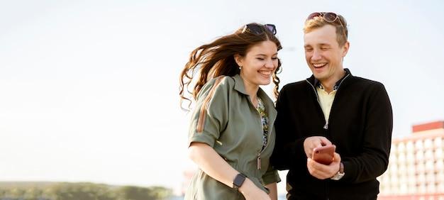 Una giovane coppia di maschi e femmine in cerca di foto dalle vacanze, divertirsi all'aria aperta