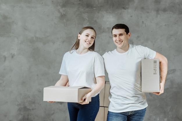 Giovani coppie uomo e donna che tengono le scatole per trasferirsi in una nuova casa.