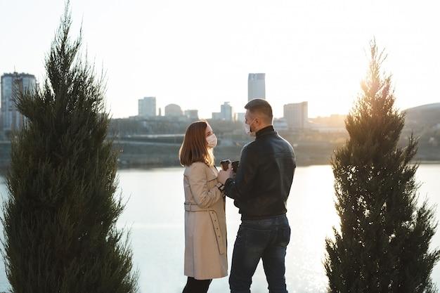 Una giovane coppia, un uomo e una donna in maschera e guanti medici, bevono caffè dalle tazze usa e getta per strada e si guardano l'un l'altro sullo sfondo del fiume e della città. quarantena