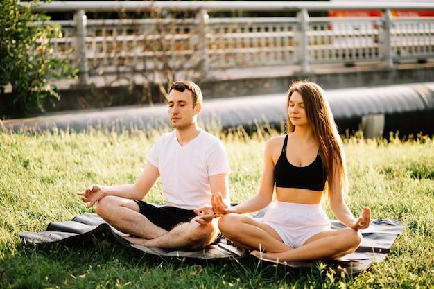 Giovane coppia uomo e donna meditare seduti nella posizione del loto, yoga sul prato della città, serate estive insieme