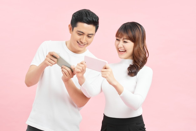 Coppia giovane uomo e donna spiata a vicenda i telefoni cellulari tenendo in mano isolate su sfondo rosa
