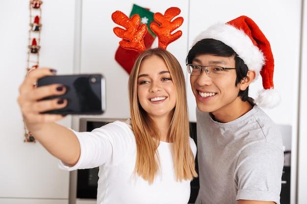 Giovane coppia, uomo e donna che indossa abiti natalizi, in piedi in cucina luminosa e scattare foto selfie sul telefono cellulare