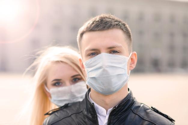 Coppia giovane in maschere sulla strada cittadina. isolamento, quarantena.
