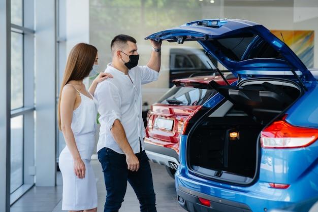 Una giovane coppia in maschera seleziona un nuovo veicolo e si consulta con un rappresentante della concessionaria nel periodo della pandemia. vendita di automobili e vita durante la pandemia.