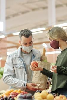 Giovane coppia in maschere in piedi al bancone e controllando la frutta insieme prima di acquistare