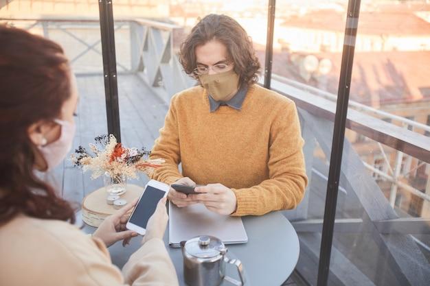 Giovane coppia in maschere utilizzando i loro telefoni cellulari mentre si incontrano nella caffetteria durante la pandemia