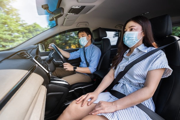 Giovane coppia in maschera medica durante la guida di un'auto. per proteggere la pandemia di covid-19 (coronavirus)