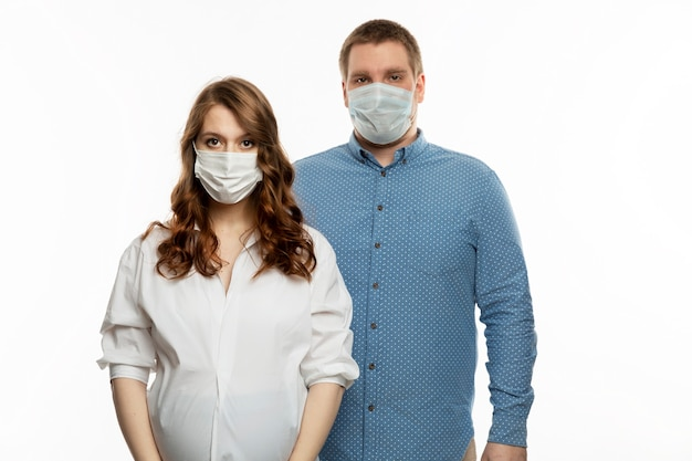 Coppia giovane in maschere mediche. donna incinta con suo marito.