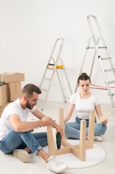 Giovani coppie che entrano nella nuova casa che si siede sul pavimento e che assemblano insieme tavolino