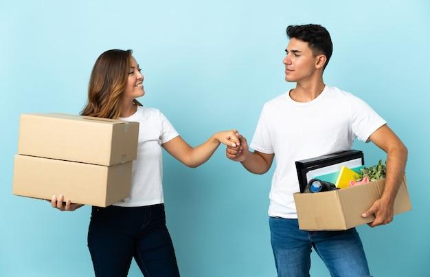 Giovani coppie che si spostano nella nuova casa tra le caselle sulla stretta di mano blu dopo un buon affare