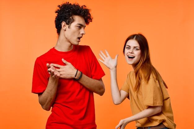 Giovane coppia in magliette multicolori gioia