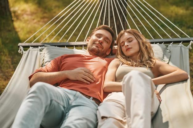 Giovane coppia che fa un pisolino sull'amaca in natura