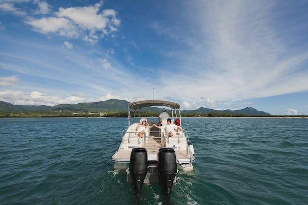 Giovani coppie che navigano su uno yacht nell'oceano indiano. bell'uomo e donna sul ponte dello yacht si trovano sulla sedia morbida